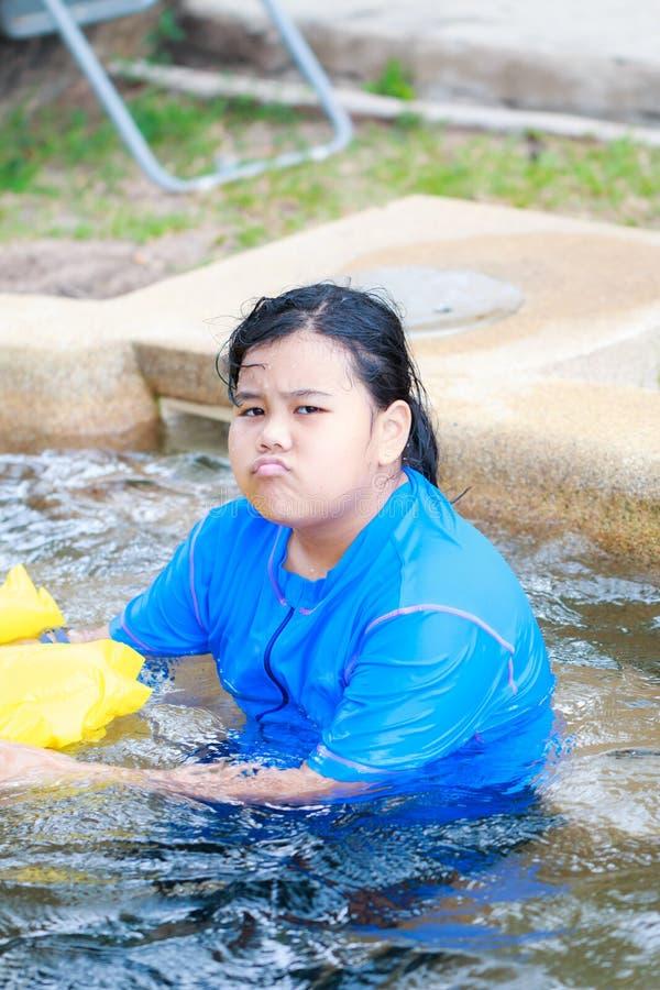 Ilsken liten asiatisk flickasimning i simbassäng fotografering för bildbyråer