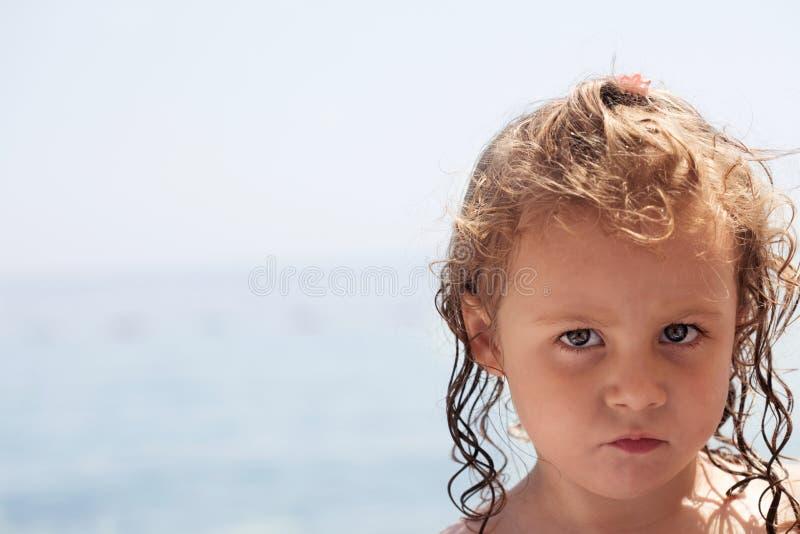Ilsken liten flicka på en familjstrandferie arkivfoto