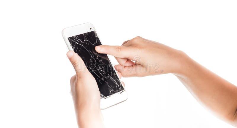 Ilsken liten flicka som rymmer en smartphone med den brutna skärmen arkivfoto