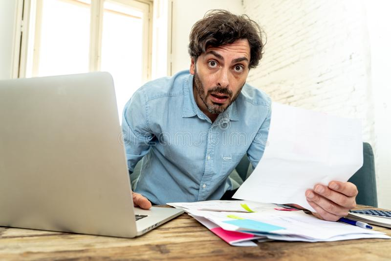 Ilsken man som betalar räkningar som hem med bärbara datorn och räknemaskinen royaltyfri bild