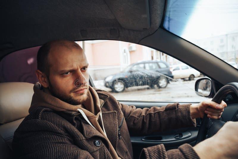 Ilsken man som kör hans bil, spänning på vägbegrepp arkivbilder