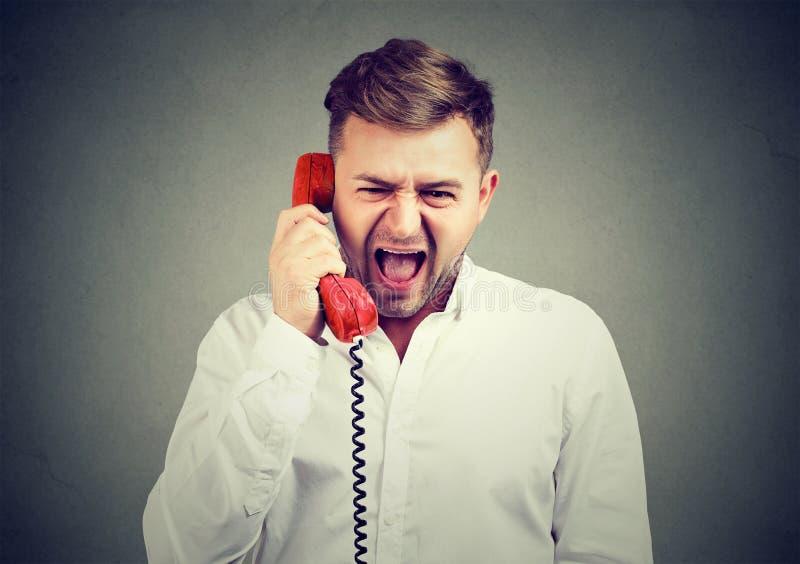 Ilsken man som screming på telefonen royaltyfri foto