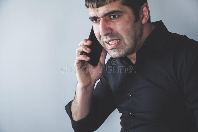 Ilsken man som talar i telefon arkivbild