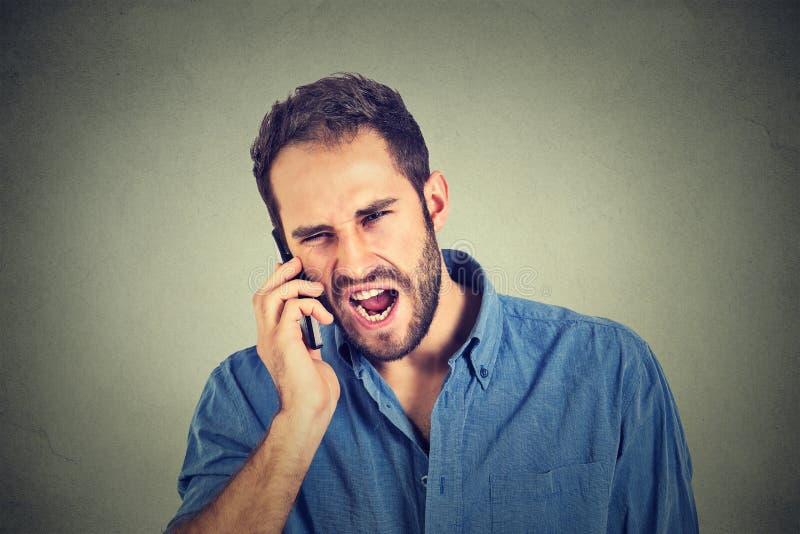 Ilsken man, tokig arbetare, skitförbannad anställd som ropar medan på telefonen arkivfoton