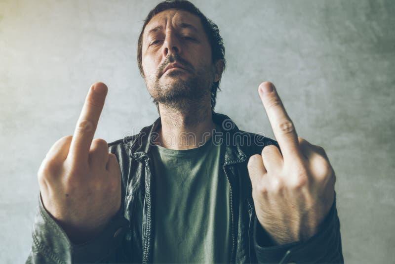 Ilsken manlig punkrockvisninglångfinger royaltyfria foton