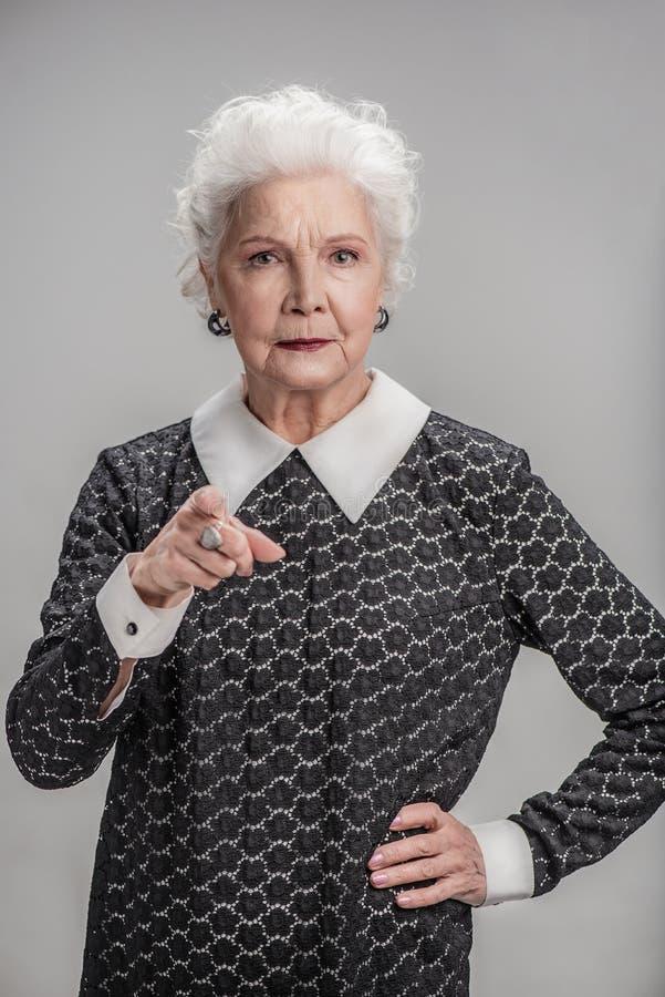 Ilsken mogen kvinna som allvarligt gör en gest fotografering för bildbyråer