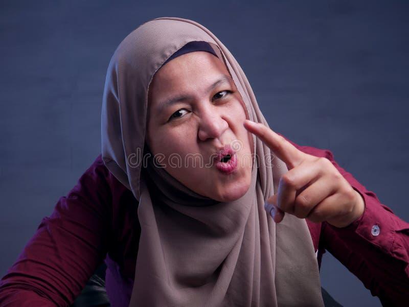 Ilsken muslimsk kvinna som ?r i huvudrollen p? kameran arkivfoton