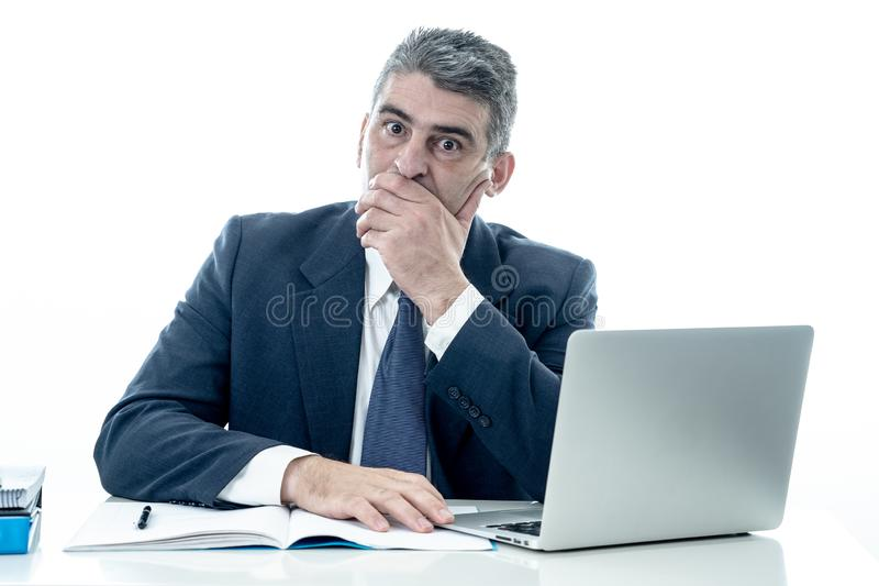 Ilsken och desperat affärsman som ropar med bärbar datordatoren och skrivbordsarbete i kuggning för spänning för affärsfolk och t royaltyfri foto