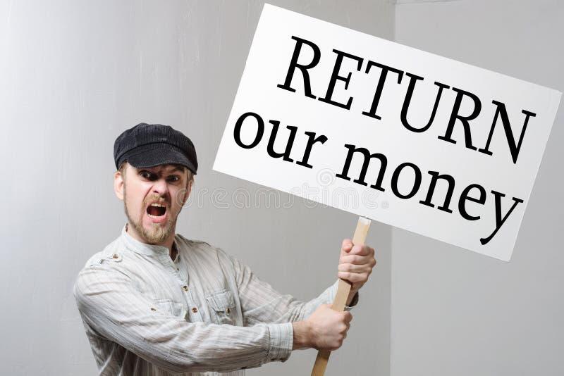 Ilsken protestera arbetare med protestteckeninskriften att gå våra pengar tillbaka arkivfoto