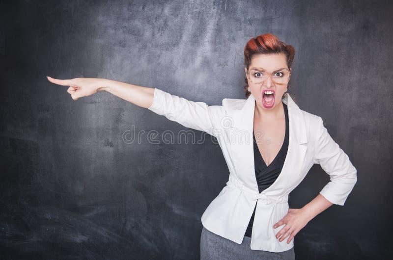 Ilsken skrikig lärare som pekar ut på svart tavlabakgrund royaltyfri bild