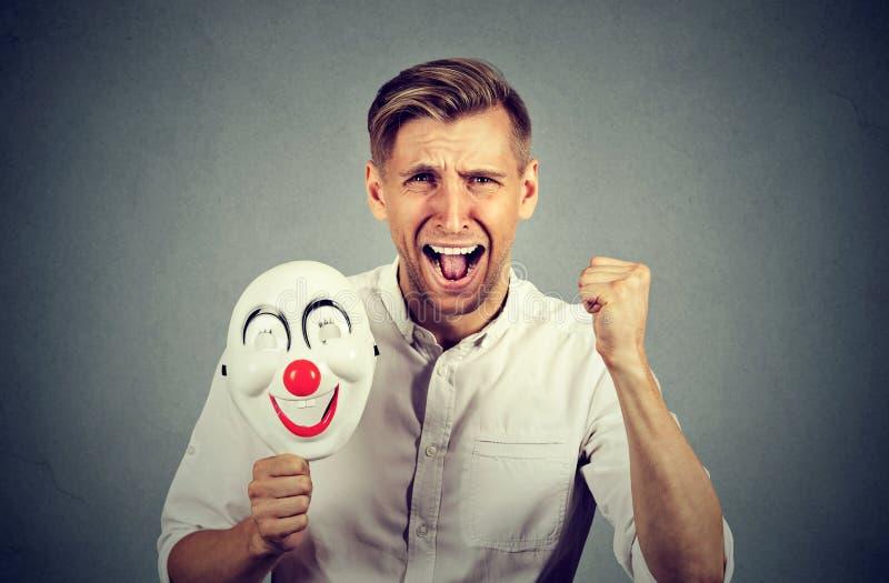 Ilsken skrikig maskering för maninnehavclown som uttrycker gladlynthetlycka royaltyfri fotografi