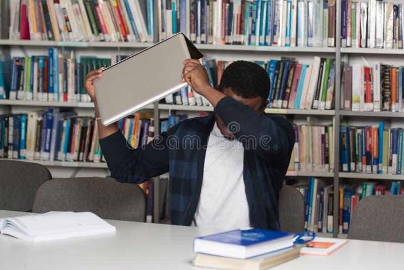 Ilsken student Wants To Break hans bärbar dator royaltyfri bild