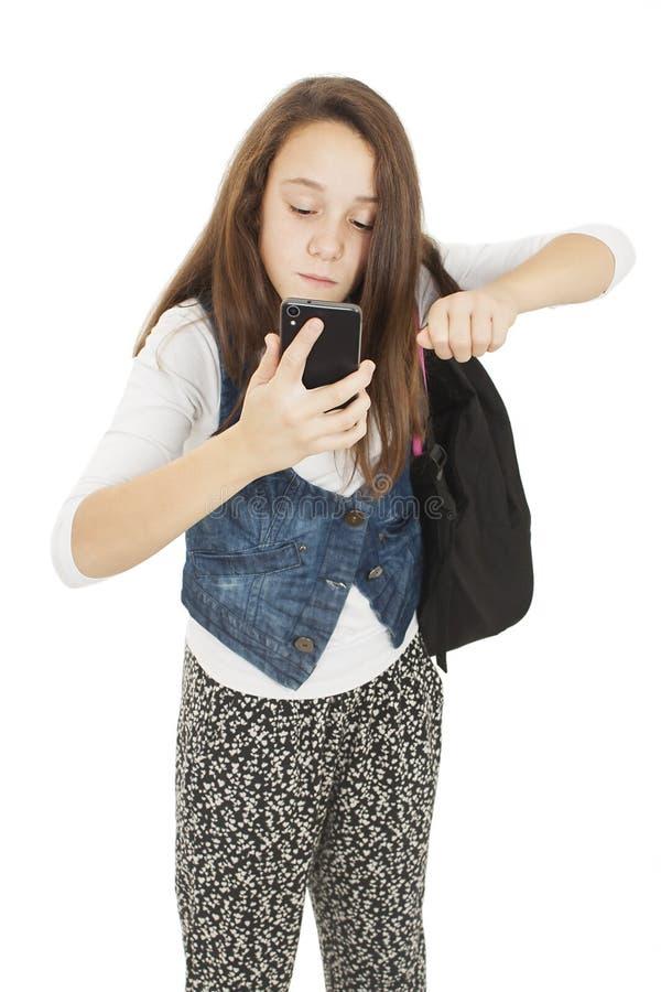 Ilsken studentflicka på telefonen med hans nävar arkivfoto