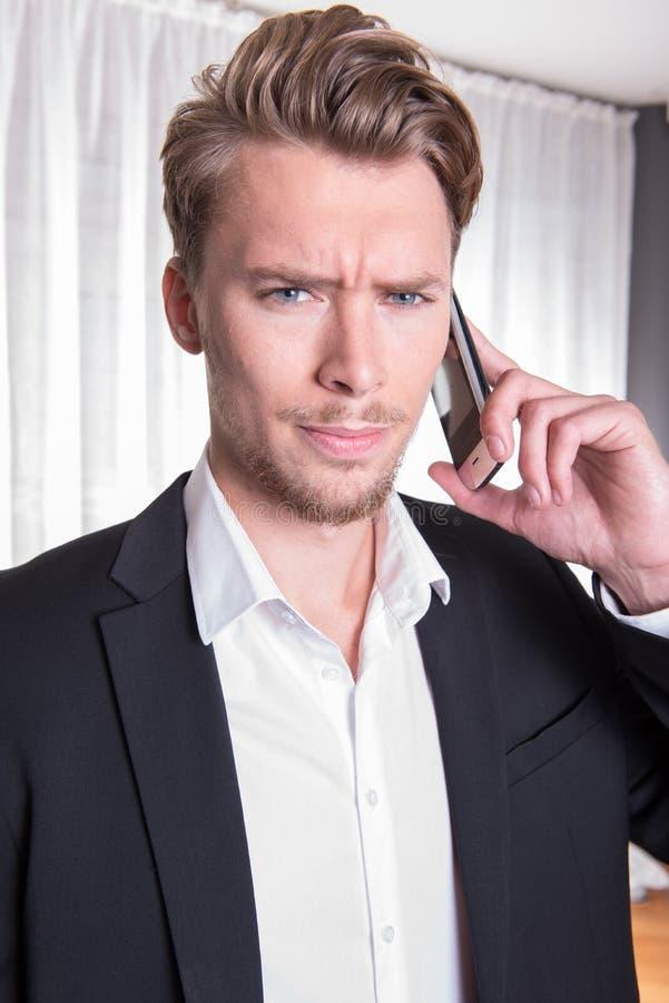 Ilsken ung affärsman för stående i dräkt på telefonen royaltyfri fotografi