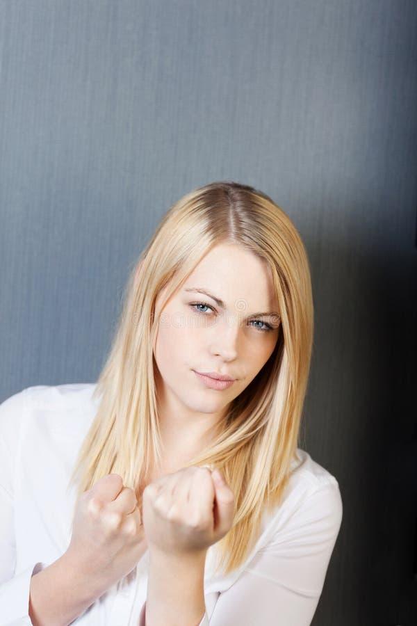 Ilsken ung kvinna med grep hårt om nävar fotografering för bildbyråer
