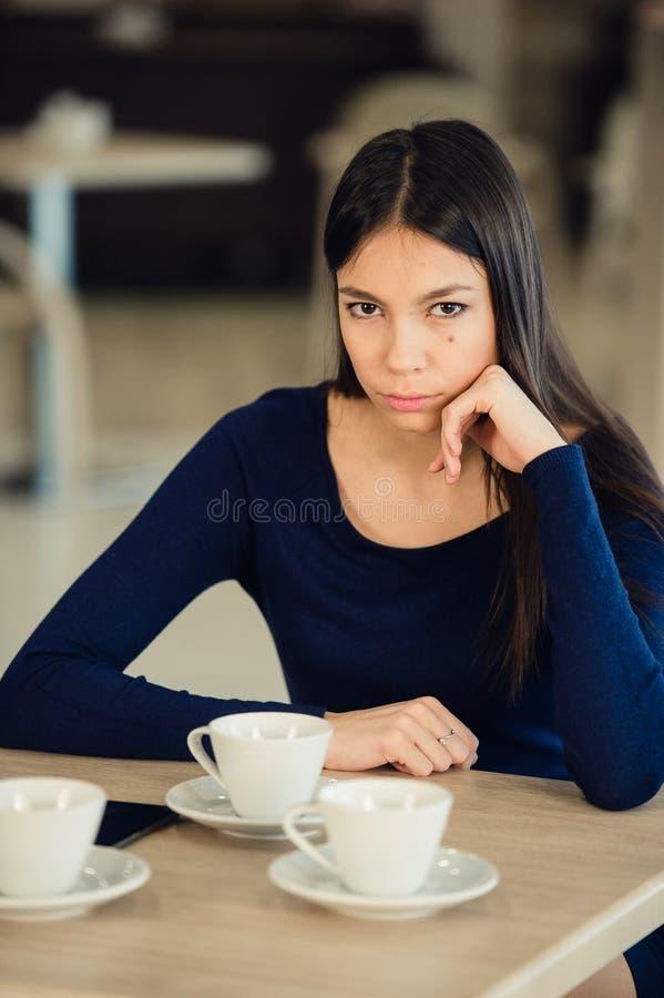 Ilsken ung kvinna med korsade armar på kafét royaltyfri foto