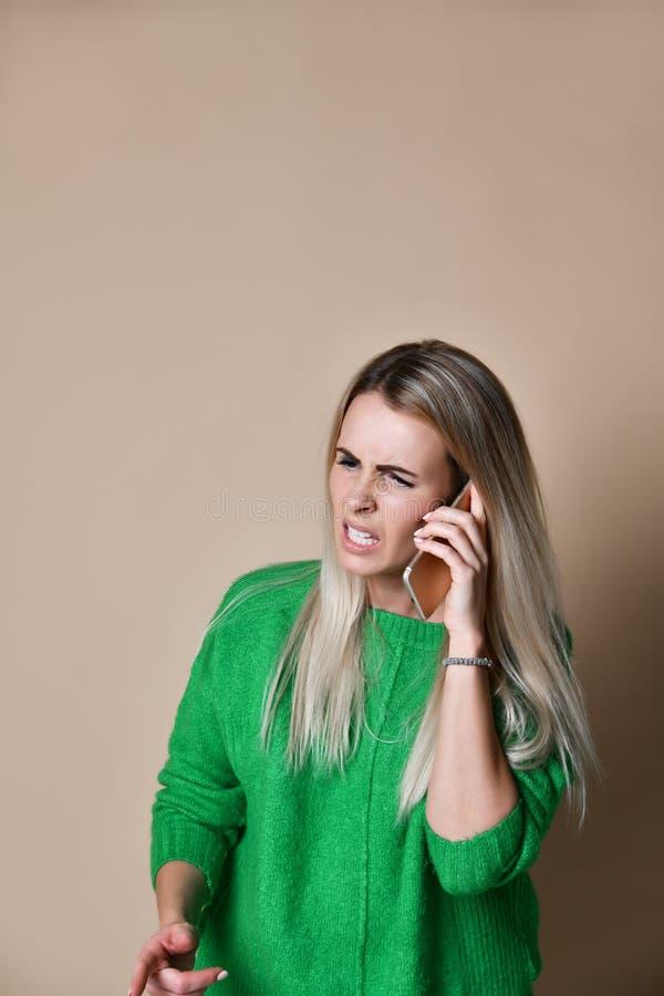 Ilsken ung kvinna som argumenterar samtal p? telefonen royaltyfria foton