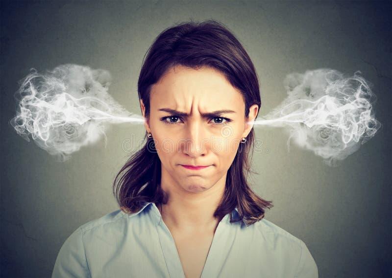 Ilsken ung kvinna som blåser ånga som kommer ut ur öron royaltyfri fotografi