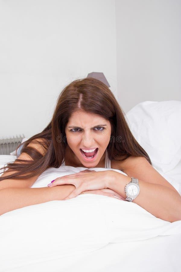 Ilsken ung kvinna som ligger på ropa för säng fotografering för bildbyråer