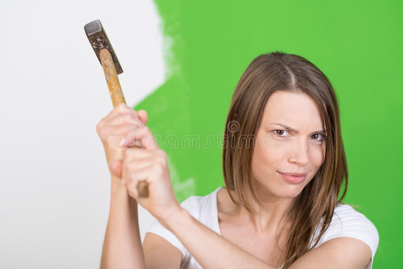 Ilsken ung kvinna som lyfter en hammare i luften fotografering för bildbyråer