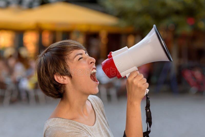 Ilsken ung kvinna som skriker in i en megafon arkivbild