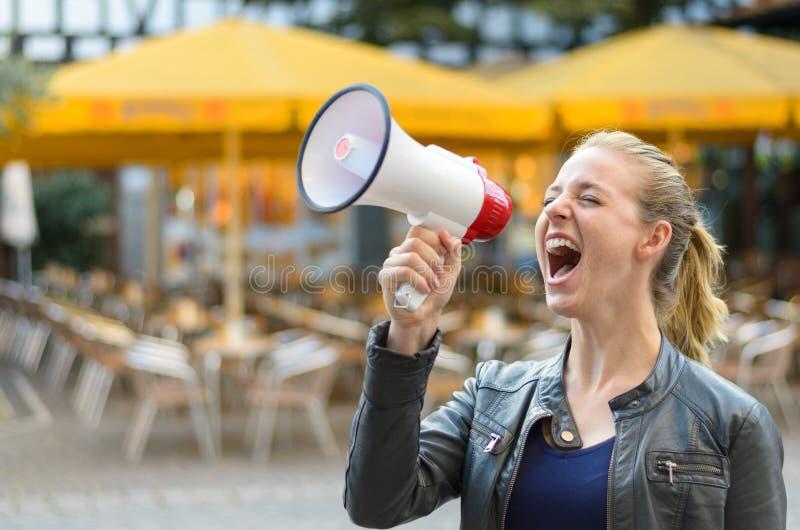 Ilsken ung kvinna som skriker in i en megafon royaltyfri foto