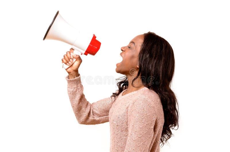 Ilsken ung kvinna som skriker in i en megafon arkivfoton