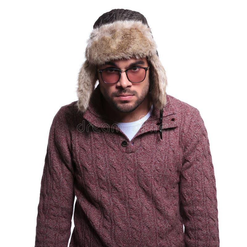 Ilsken ung man i vinterkläder och pälshatt fotografering för bildbyråer