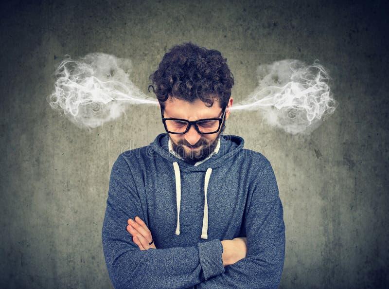 Ilsken ung man som blåser ånga som kommer ut ur öron, omkring att ha nervsammanbrottet arkivfoto