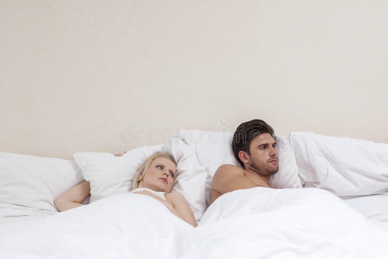 Ilsken ung man som ignorerar kvinnan i säng royaltyfri fotografi
