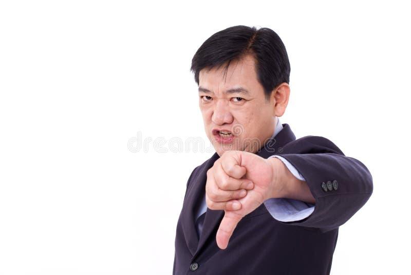Ilsken, uppriven allvarlig affärsman som ner ger tummen arkivfoto