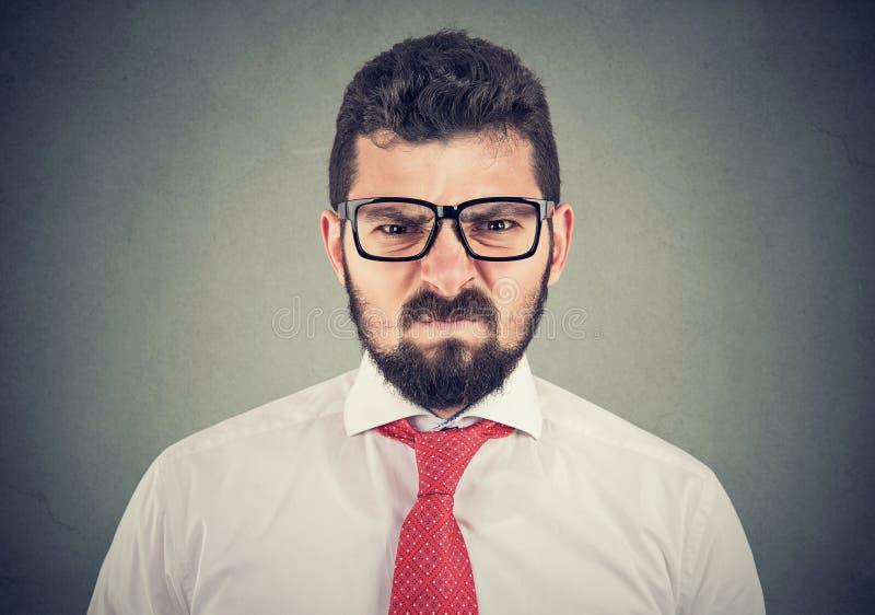 Ilsken vresig man som ser mycket missn?jd arkivfoto
