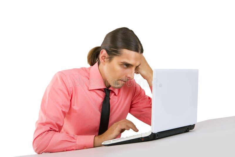 Ilsken vresig ung man med bärbara datorn som ser bildskärmen över w arkivbild