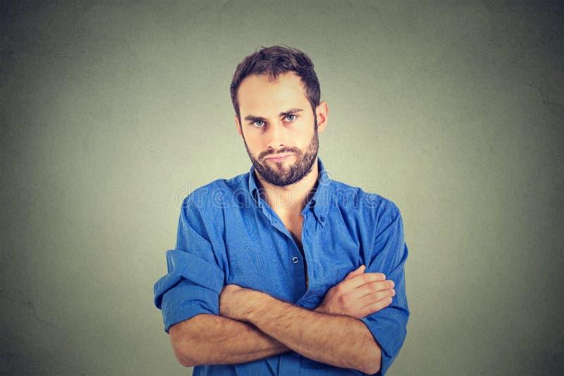 Ilsken vresig ung man som ser mycket missnöjd arkivfoton
