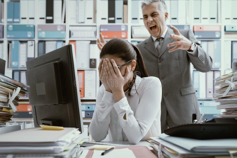 Ilsket framstickande som skriker på hans unga anställd arkivfoton