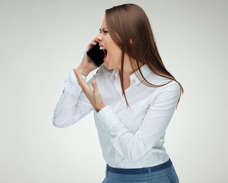 Ilsket kvinnaframstickande som ropar med telefonen arkivbilder