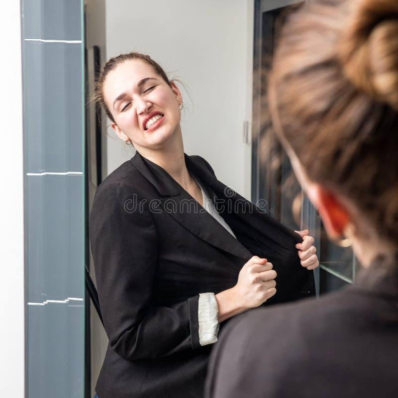 Ilsket smart förlorande humör för ung kvinna framme av hennes spegel arkivbild