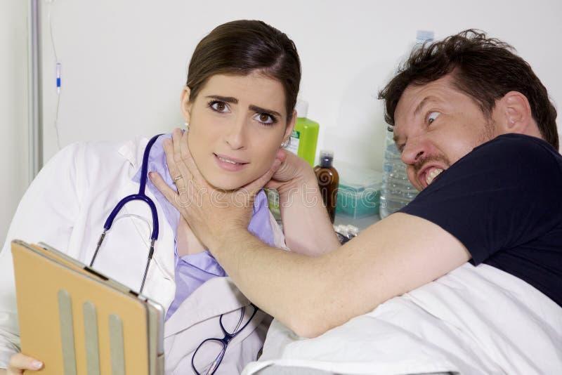 Ilsket tålmodigt försöka att döda doktorn i sjukhus royaltyfria foton