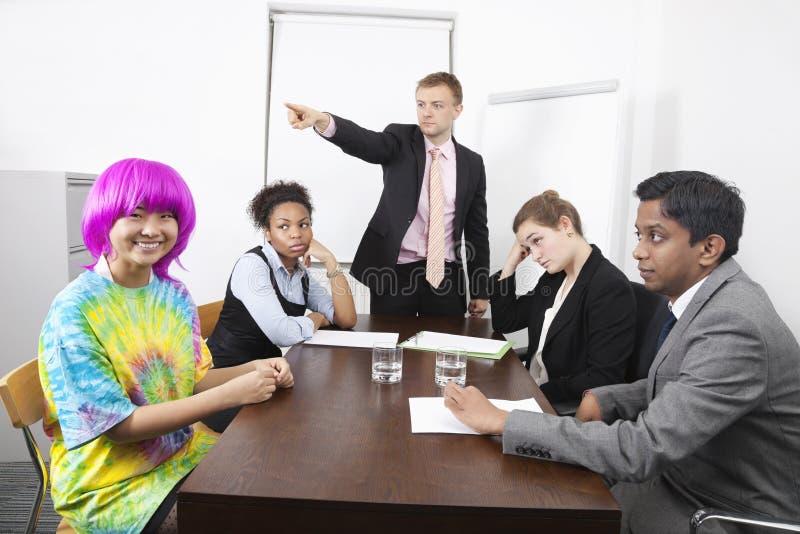 Ilskna multietniska businesspeople med kollegan i rosa peruk på mötet arkivbilder