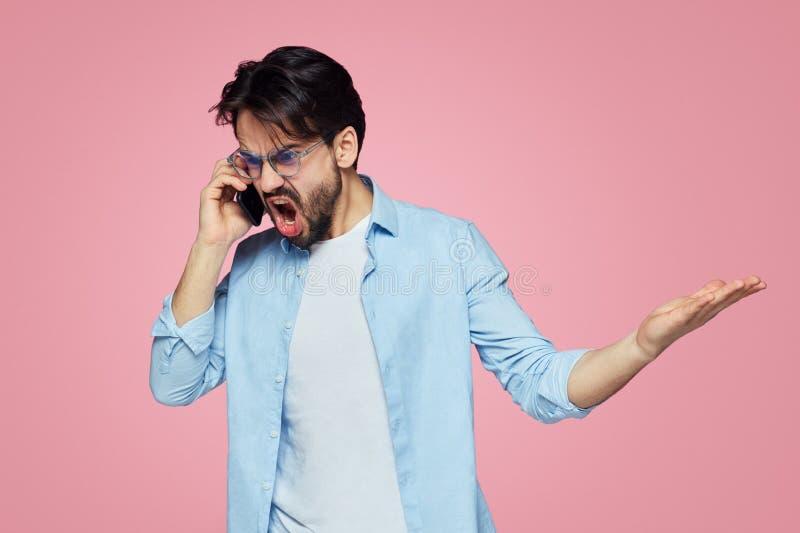 Ilskna rasande mangester med förargat uttryck, skrin högt, medan ha mobil konversation, poserar mot den rosa bakgrunden royaltyfri foto