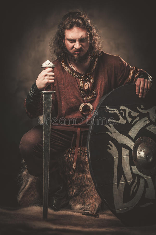 Ilskna viking med svärdet i traditionell kläder för en krigare som poserar på en mörk bakgrund royaltyfri foto