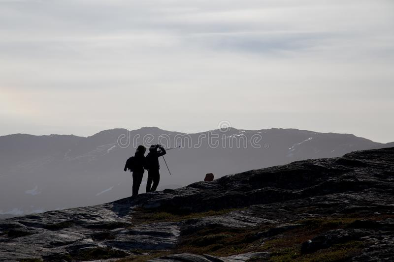 Silhouette of two hikers. Ilulissat, Greenland - July 8, 2018: Silhouette of two hikers in a rocky landscape royalty free stock photo