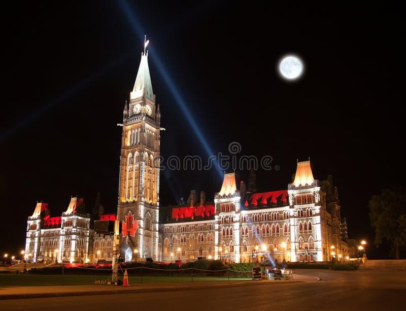 A iluminação da casa canadense do parlamento na noite imagens de stock