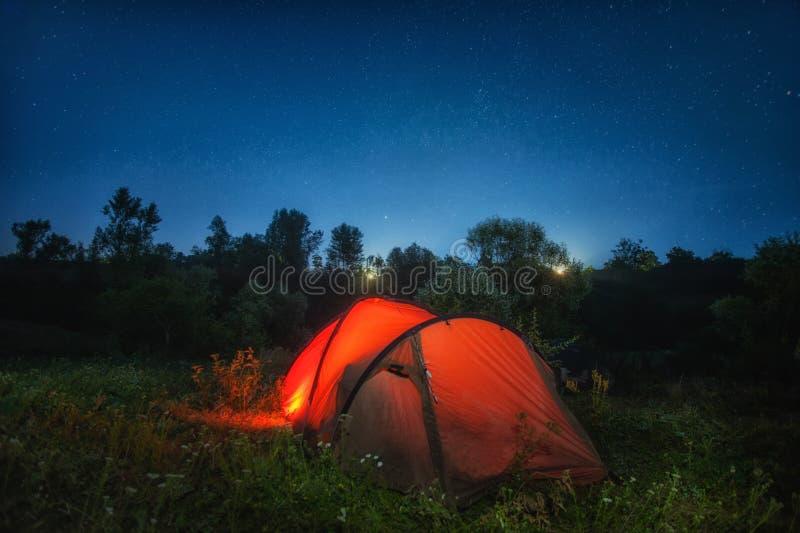 Iluminação vermelha da barraca para dentro sob o céu noturno fotografia de stock