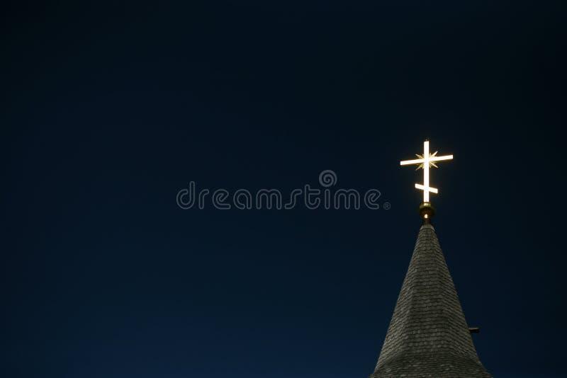 Iluminación de la cruz ortodoxa en un cielo azul fotografía de archivo