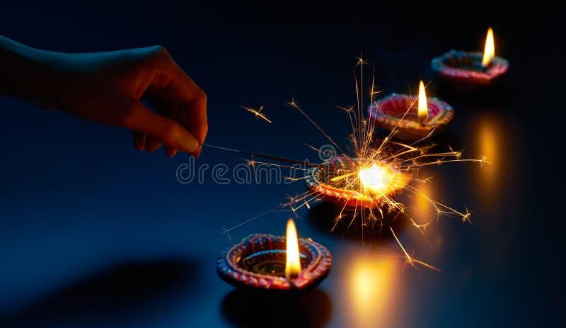 Iluminación de una bengala con la lámpara del diya imagen de archivo libre de regalías