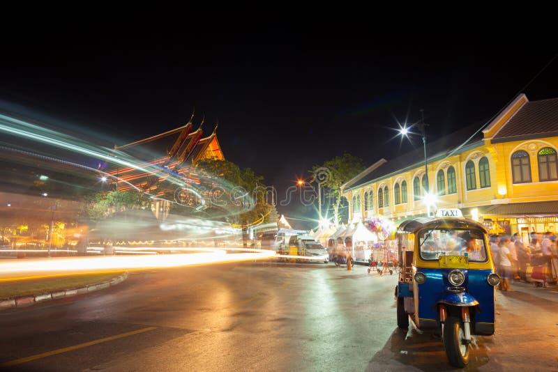 Iluminación del tráfico de la noche con el estacionamiento del ` de Tuk Tuk del ` en la cartilla de ahorros imagen de archivo libre de regalías