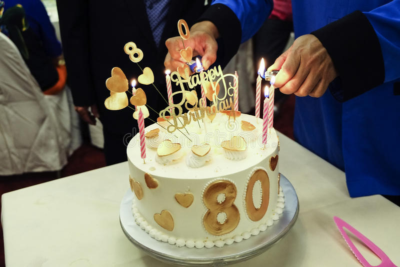 Iluminación encima de velas en la torta de cumpleaños fotografía de archivo libre de regalías