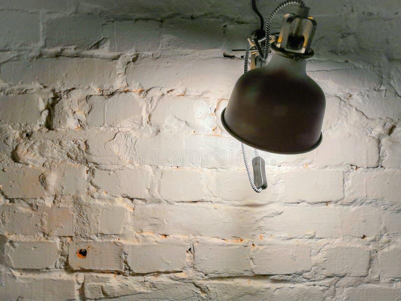 Iluminando a lâmpada em uma parede de tijolo branca foto de stock
