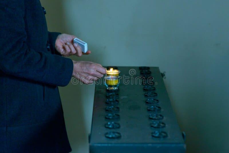 Iluminando uma vela votiva na igreja imagem de stock royalty free